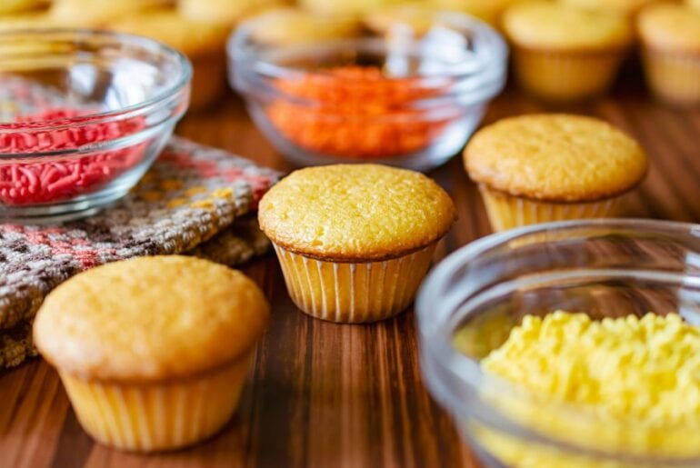 Three Mini Cupcakes With Bowls of Sprinkles
